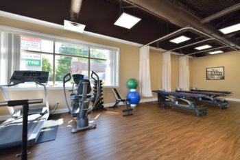 Physiotherapy exercising room with a treadmill, treatment beds, and an elliptical machine