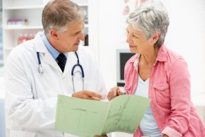 A physiotherapist discussing chronic pain management with an elderly patient.