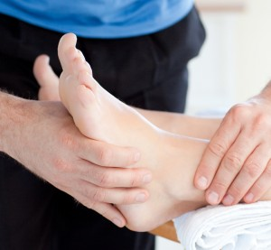 Physiotherapist examining a patient's foot for custom orthotics