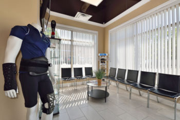 The waiting room for the HealthMax Physiotherapy clinic with chairs and a mannequin wearing physio-therapeutic equipment